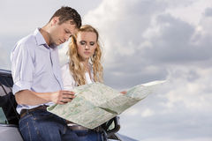 Couple reading map while leaning on car against cloudy sky Stock Photo
