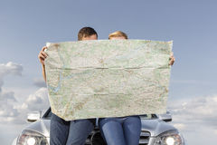 Couple reading map while leaning on car hood during road trip Royalty Free Stock Photos