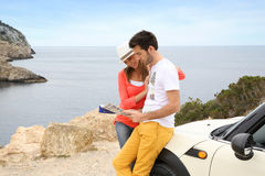 Couple reading map on road trip Stock Images