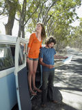 Couple Reading Map During Road Trip. Full length of happy young women standing in campervan door with men looking at map during road trip stock photo