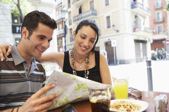 Couple Reading Map At Sidewalk Cafe Royalty Free Stock Photography