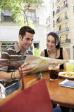 Couple Reading Map At Sidewalk Cafe Stock Photo