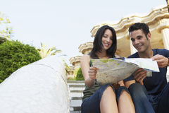 Couple Reading Map On Steps Royalty Free Stock Image