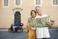 Couple Reading Map On Street. Happy couple reading map on street in Rome; Italy Royalty Free Stock Photos