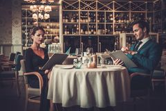 Couple reading menu in a restaurant stock photography