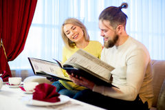Couple reading a menu in a restaurant Stock Image