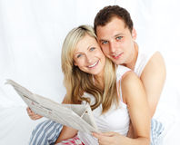 Couple reading a newspaper in bed Stock Photography