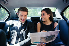 Couple reading newspaper in car Stock Images