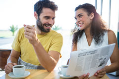 Couple reading newspaper while having coffee Stock Image