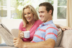 Couple Reading Newspaper At Home Stock Photos