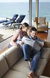 Couple Reading Newspaper In Living Room stock photography