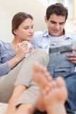Couple reading a newspaper while lying on a sofa Stock Photography