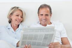 Couple reading newspaper. Portrait Of Mature Couple Reading Newspaper Together At Home Stock Photography