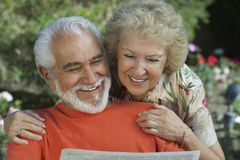 Couple Reading Newspaper Together Stock Photo