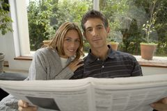 Couple reading newspaper together Royalty Free Stock Photo
