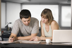 Couple Reading Newspaper Together At Counter Royalty Free Stock Images