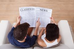 Couple reading newspaper together on sofa Stock Image