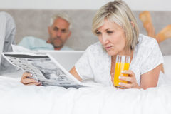 Couple reading newspaper and using laptop in bed Royalty Free Stock Image