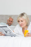 Couple reading newspaper and using laptop in bed Stock Photo