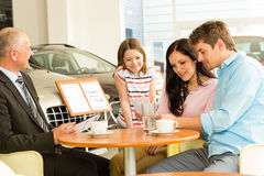 Couple reading papers in car dealership Stock Photography