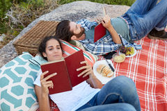 Couple reading during a picnic on the rocks, at the seaside Stock Photo