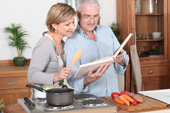 Couple reading a recipe book Royalty Free Stock Images
