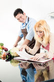 Couple reading recipes in cook book Stock Photos