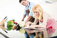 Couple reading recipes in cook book Stock Image