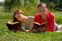 Couple reading and relaxing at the park. Stock Photography