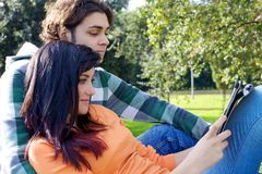 Couple reading tablet in park Royalty Free Stock Images