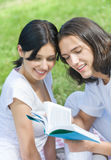 Couple reading a textbook outdoors Royalty Free Stock Photo