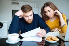 Couple reading their bills at home Royalty Free Stock Photos