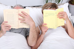 Couple reading together in bed Royalty Free Stock Images