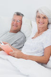 Couple reading together in bed Royalty Free Stock Photos