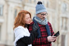 Couple reads message in smart-phone. Woman embraces man with cellular. Guy in hat and glasses received SMS. stock photos
