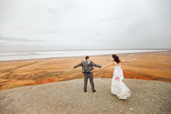 Couple ready to jump on the mountain. Bride and groom on the mountain ready to jump Royalty Free Stock Images