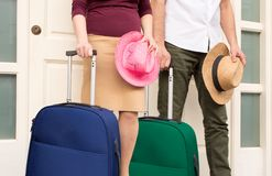 The couple is ready to the vacations. The couple at the doorway of home  is waiting to the taxi with suitcases Stock Photo