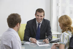 Couple With Real Estate Agent In Office Stock Image