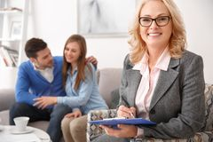 Couple at real estate sales office with agent holding paper holder stock photography