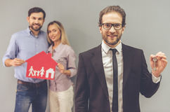 Couple and a realtor. Handsome realtor in suit is holding keys, looking at camera and smiling while happy beautiful couple is holding paper house in the Stock Image