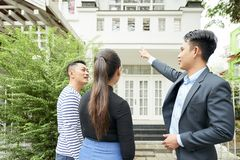 Couple with realtor looking at new house stock photo