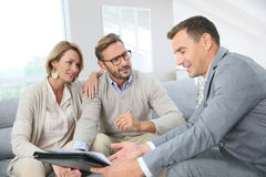 Couple with realtor signing contract. Couple with realtor signing mortgage contract Stock Photos