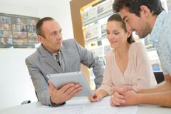 Couple and realtor using tablet Stock Photography