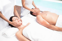 Couple receiving a face massage from masseur Stock Photography