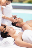 Couple receiving a head massage from masseur. In a spa royalty free stock image