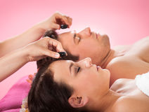 Couple Receiving Hot Stone Massage At Spa Stock Photo