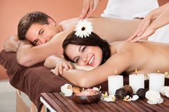 Couple receiving shoulder massage at spa Stock Image