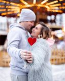 Couple with red candy heart on Christmas market looking at each other stock photography