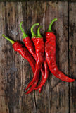 A couple of Red chili peppers. Closeup of red Hot chili pepper pod on a wooden desk royalty free stock photography
