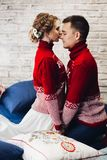 Couple in red Christmas jumpers kissing surrounded by pillows. royalty free stock photo